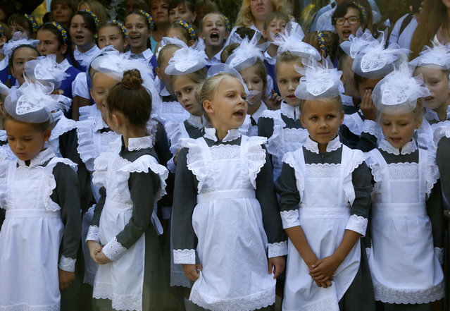Schoolgirls in traditional uniforms as they attend a ceremony on the occasion of the first day of school at a cadet lyceum in Kyiv, Ukraine, Monday, September 2, 2019. (Photo by Efrem Lukatsky/AP Photo)