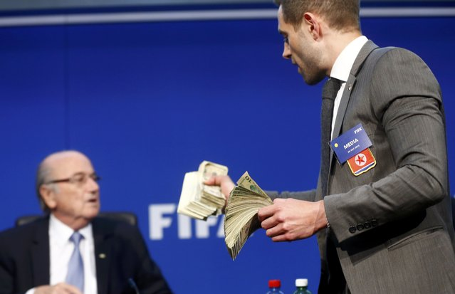 British comedian known as Lee Nelson holds banknotes in front of FIFA President Sepp Blatter (L) at a news conference after the Extraordinary FIFA Executive Committee Meeting at the FIFA headquarters in Zurich, Switzerland July 20, 2015. (Photo by Arnd Wiegmann/Reuters)