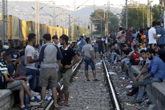 In this photo taken on Thursday, July 23, 2015 migrants from Middle East, Asia and Africa wait to board a train to Serbia at the railway station in the southern Macedonian town of Gevgelija. (Photo by Boris Grdanoski/AP Photo)