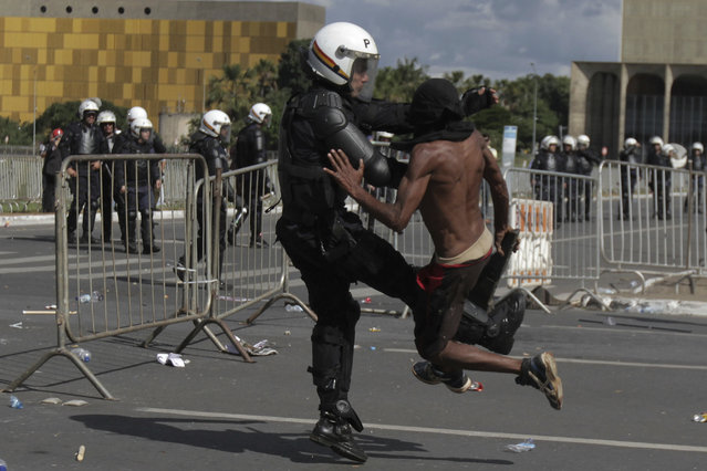 A demonstrator clashes with a police officer during an anti-government protest in Brasilia, Brazil, Wednesday, May 24, 2017. (Photo by Eraldo Peres/AP Photo)