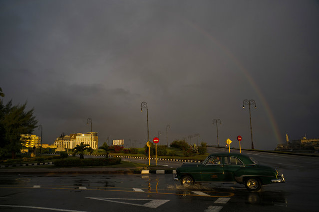 In this November 10, 2019 photo, under a rainbow, a man drives a classic American car past the newly opened Hotel Paseo del Prado in Havana, Cuba. (Photo by Ramon Espinosa/AP Photo)