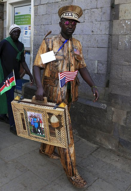 A man wearing a suit and carrying a briefcase all made from the dried bark leaf of a banana tree, arrives at the Memorial Park to pay his respects shortly after U.S. President Barack Obama laid a wreath in honor of those who died after an al Qaeda attack in 1998 at the compound of the former U.S. Embassy leaving more than 200 people dead, in Kenya's capital Nairobi July 25, 2015. (Photo by Noor Khamis/Reuters)