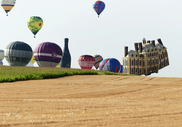 """Hot-air balloons fly near Chambley-Bussieres, eastern France, on July 26, 2015, on the first day of the international air-balloon meeting """"Lorraine Mondial Air Ballons"""". (Photo by Jean-Christophe Verhaegen/AFP Photo)"""