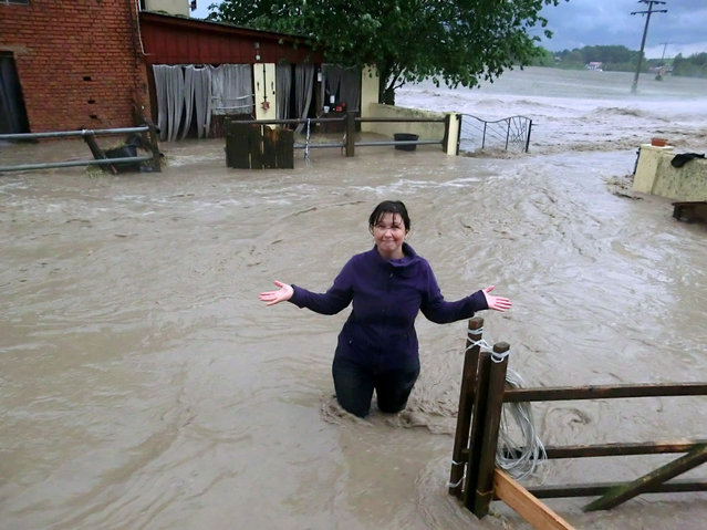 A woman stands amidst the water flooding a horse farm in Obernzenn, southern Germany, after a thunderstorm hit the region on May 29, 2016. Four people died and several more were injured in southern Germany after violent storms with torrential rains caused severe flooding, authorities said. (Photo by Vera Groeschl/AFP Photo/DPA)