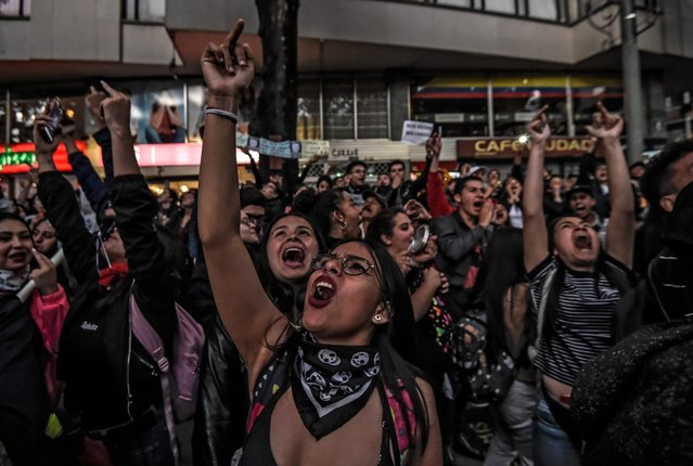 Students give the middle finger as they shout slogans during a vigil for Dilan Cruz, a young demonstrator who had been wounded by a member of the Mobile Anti-Disturbance Squadron (ESMAD) during a protest against the Colombian government and died yesterday, in Bogota on November 26, 2019. Under-fire Colombian President Ivan Duque will meet with protest leaders on Tuesday, a minister announced, after five consecutive days of anti-government protests. The meeting will form part of the national dialogue Duque launched on Sunday to address corruption, economic inequality and other woes. (Photo by Juan Barreto/AFP Photo)