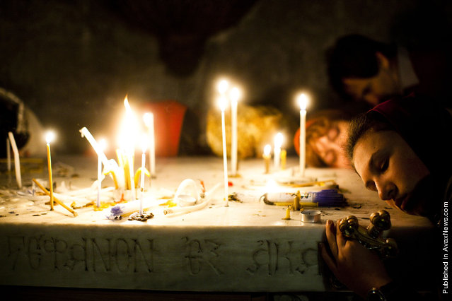 Christian pilgrims pray at Church of the Holy Sepulcher during the Good Friday procession in Jerusalem, Israel