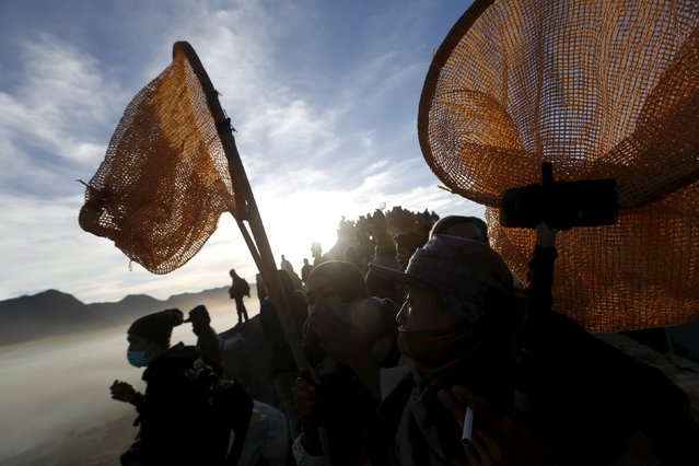 Villagers holds their nets as they wait for Hindu worshippers to throw their offerings into the crater during the Kasada Festival at Mount Bromo in Probolinggo, Indonesia's East Java province, August 1, 2015. (Photo by Reuters/Beawiharta)