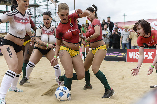"""p*rn actresses play football as they wear only body painted jerseys in the colors of the German and Ghanaian national football teams during a promotional event called """"Sexysoccer 2014"""" on June 21, 2014 in Berlin, few hours before the World Cup 2014 football match Germany vs Ghana to be played in Brazil. (Photo by Clemens Bilan/AFP Photo)"""
