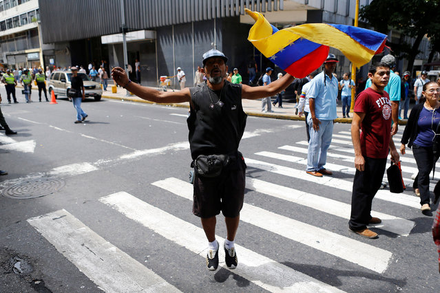 A supporter of Venezuela's President Nicolas Maduro shouts slogans against opposition lawmakers during a protest at the area of the elections council headquarters in Caracas, Venezuela, June 9, 2016. (Photo by Ivan Alvarado/Reuters)