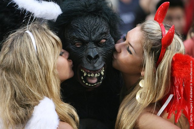 Rugby fans kiss a fellow spectator wearing a gorilla mask during the Hong Kong Rugby Sevens 2008 on March 28, 2008 in Hong Kong, China