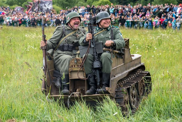 "Military history enthusiasts dressed as Nazi  Germany's troops take part  in a stage battle ""Summer 1941"" near the village of Ivanovskoye, some 60 km outside  Moscow, on June 22, 2014, during ""War of Motors 2014"" festival marking the 73d anniversary  of the  Nazi Germany invasion of the Soviet Union. (Photo by Dmitry Serebryakov/AFP Photo)"