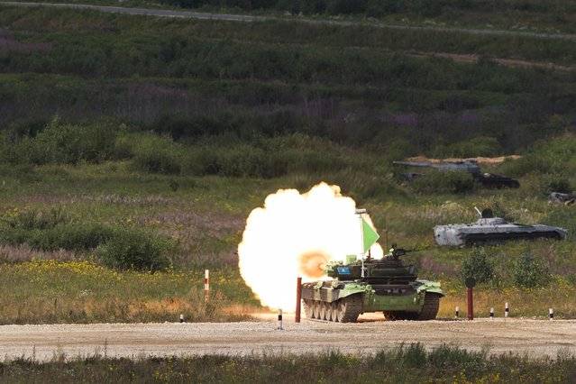 A Kazakhstan tank fires it's main armament during competition in Alabino, outside Moscow, Russia, Monday, August 3, 2015. (Photo by Pavel Golovkin/AP Photo)