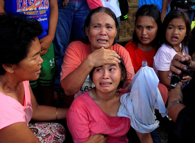 Residents who want to evacuate from their homes gather while waiting for a vehicle after Islamist militants, who had holed up in a primary school, retreated after a gunbattle with troops but were holding some civilians hostage, in Pigcawayan, North Cotabato, Philippines June 21, 2017. (Photo by Marconi Navales/Reuters)