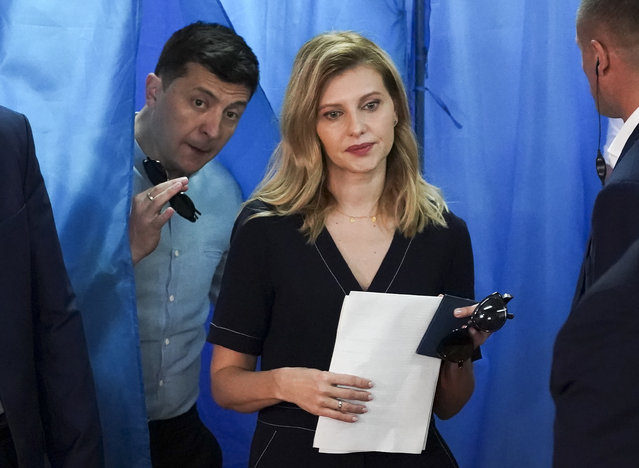 Ukrainian President Volodymyr Zelenskiy, ,left, and his wife Olena Zelenska leave a booth at a polling station during a parliamentary election in Kiev, Ukraine, Sunday, July 21, 2019. Ukrainians are voting in an early parliamentary election in which the new party of President Volodymyr Zelenskiy is set to take the largest share of votes. (Photo by Evgeniy Maloletka/AP Photo)
