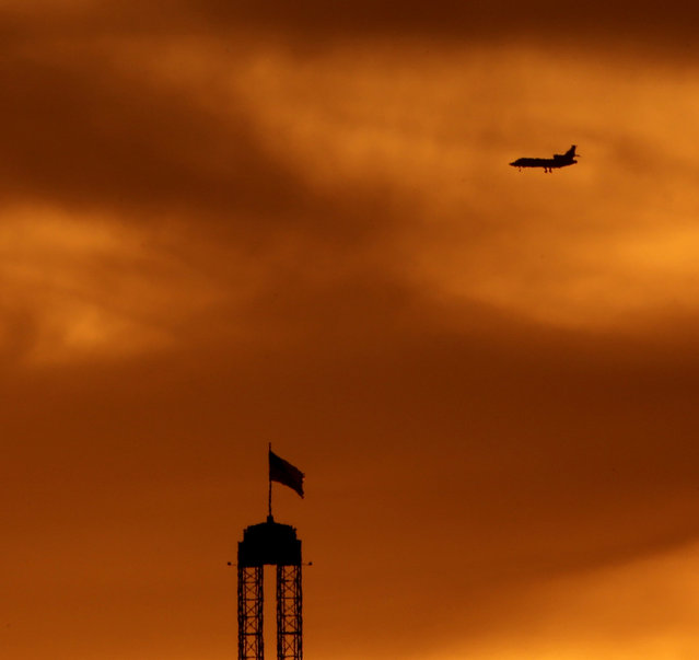 A plane is silhouetted as the sun sets beyond Worlds of Fun amusement park, Thursday, July 30, 2015, in Kansas City, Mo. (Photo by Charlie Riedel/AP Photo)
