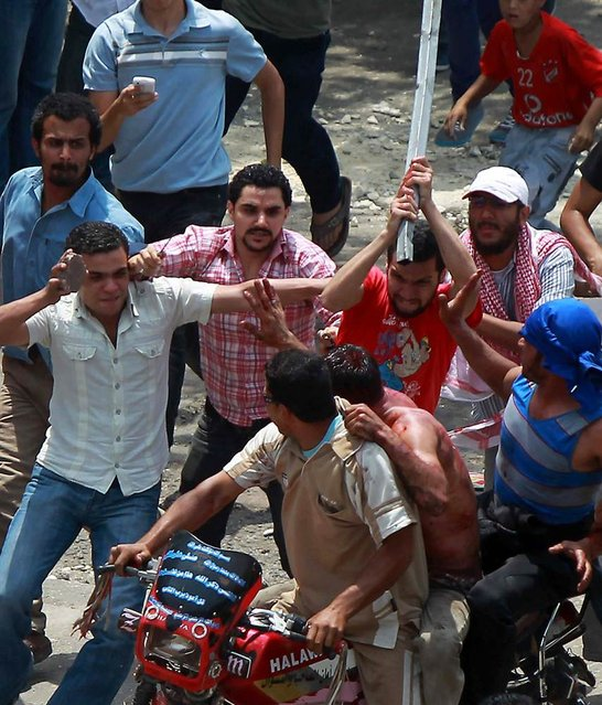 Egyptian protesters beat a man as he tries to escape on the back of a motorcycle after he was accused of attacking demonstrators in the Abbassiya district of Cairo on May 2