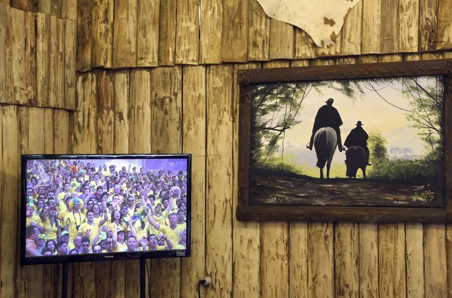 """A painting showing gauchos riding horses hangs on the wall near a television during the 2014 World Cup match between Brazil and Chile being played in Belo Horizonte, in the Farroupilha camp in Porto Alegre, June 28, 2014. In a project called """"On The Sidelines"""" Reuters photographers share pictures showing their own quirky and creative view of the 2014 World Cup in Brazil. (Photo by Stefano Rellandini/Reuters)"""