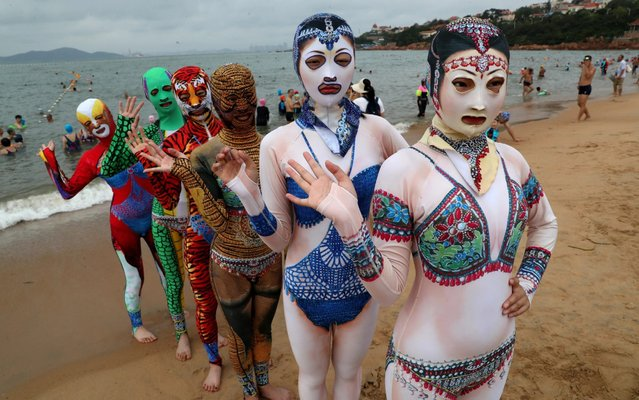 Models wearing facekinis, popular with female bathers who want to protect more than just their modesty, pose for a picture on a beach on August 5, 2019 in the Chinese seaside city of Qingdao, Shandong Province of China. (Photo by Xu Chongde/VCG via Getty Images)
