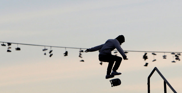 Shoes hang from a power line as a man rides his board in a park in Prague, Czech Republic, November 13, 2016. (Photo by David W. Cerny/Reuters)
