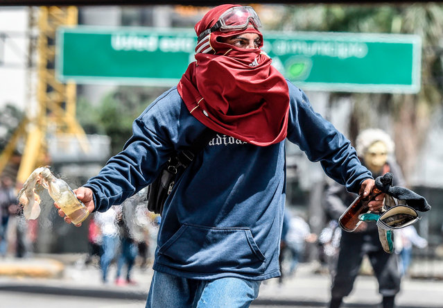 A Venezuelan opposition activist clashes with riot police during a protest against Venezuelan President Nicolas Maduro in Caracas on July 10, 2017. Venezuela hit its 100 th day of anti- government protests Sunday, amid uncertainty over whether the release from prison a day earlier of prominent political prisoner Leopoldo Lopez might open the way to negotiations to defuse the profound crisis gripping the country. (Photo by Juan Barreto/AFP Photo)