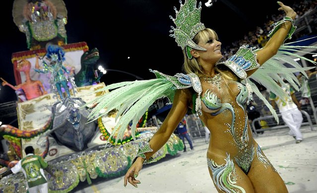 A reveller of the Mancha Verde samba school dances in front of a float at the Sambadrome