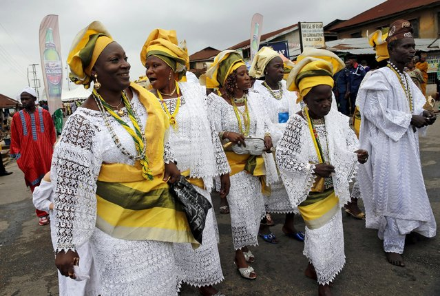 Devotees of the river goddess Osun dance down  a street during the traditional town cleansing procession at the start of the annual Osun festival in Osogbo in Nigeria's southwest, August 10, 2015. (Photo by Akintunde Akinleye/Reuters)