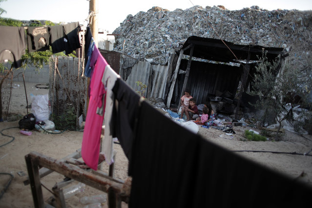 In this Monday, June 20, 2016 photo, Palestinian kids sit in front of their home in el-Zohor slum, on the outskirts of Khan Younis refugee camp, southern Gaza Strip. (Photo by Khalil Hamra/AP Photo)