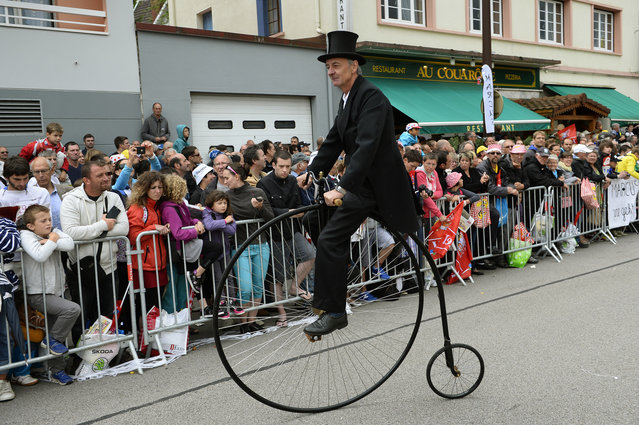A man rides a high wheeler bicycle at the departure village in Gerardmer before the start of the 170 km ninth stage of the 101st edition of the Tour de France cycling race on July 13, 2014 between Gerardmer and Mulhouse, eastern France. (Photo by Lionel Bonaventure/AFP Photo)