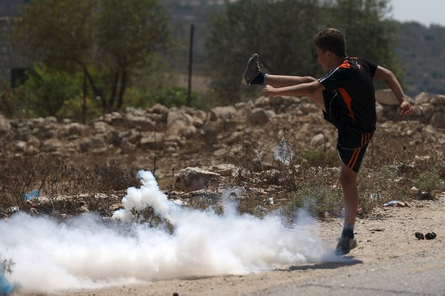 A Palestinian boy kicks a tear gas canister fired by Israeli troops during clashes at a protest in solidarity with Palestinian detainee Mohammed Allan, in the West Bank village of Nabi Saleh, near Ramallah August 14, 2015. (Photo by Mohamad Torokman/Reuters)