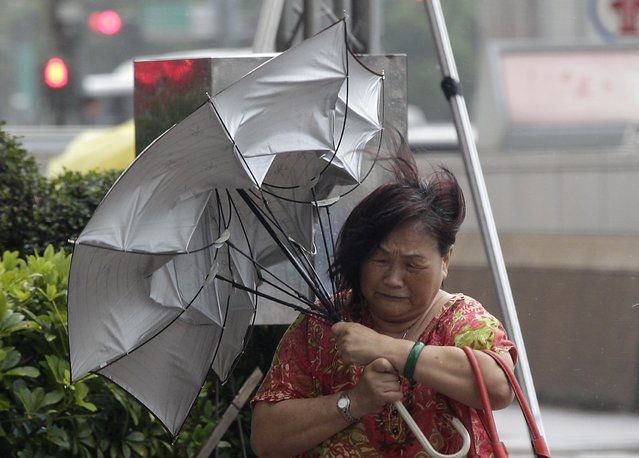 A woman holds her umbrella while walking against strong winds as Typhoon Matmo hits Taiwan, in Taipei July 23, 2014. Typhoon Matmo slammed into Taiwan on Wednesday with heavy rains and strong winds, shutting financial markets and schools, with at least one person killed and some damage reported. (Photo by Pichi Chuang/Reuters)