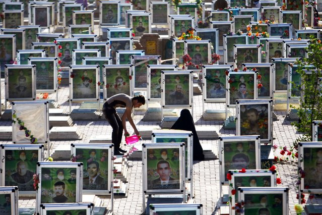 Iraqi Shiites clean the grave of a relative at one of the world's biggest cemeteries in the holy city of Najaf, on July 29, 2014, during the Eid al-Fitr celebrations marking the end of the Muslim fasting month of Ramadan. (Photo by Haidar Hamdani/AFP Photo)