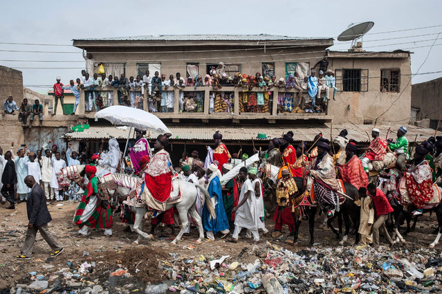 The Emir of Kano, Muhammadu Sanusi II, rides a horse as he parades with his entourage and musicians on the streets of Kano, northern Nigeria on July 6, 2016, during the Durbar Festival celebrating the Eid al-Fitr which marks the end of the Islamic holy fasting month of Ramadan. (Photo by Stefan Heunis/AFP Photo)