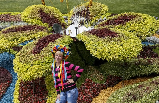 A visitor poses for a picture at a flower exhibition in Kiev, Ukraine, August 21, 2015. (Photo by Gleb Garanich/Reuters)