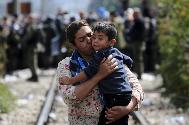 A woman carries a boy after crossing Greece's border into Macedonia near Gevgelija, Macedonia, August 22, 2015. (Photo by Ognen Teofilovski/Reuters)