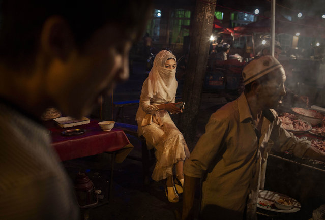 A veiled Uyghur woman sits at a food stall at a local market on August 1, 2014 in Kashgar, Xinjiang Province, China. (Photo by Kevin Frayer/Getty Images)