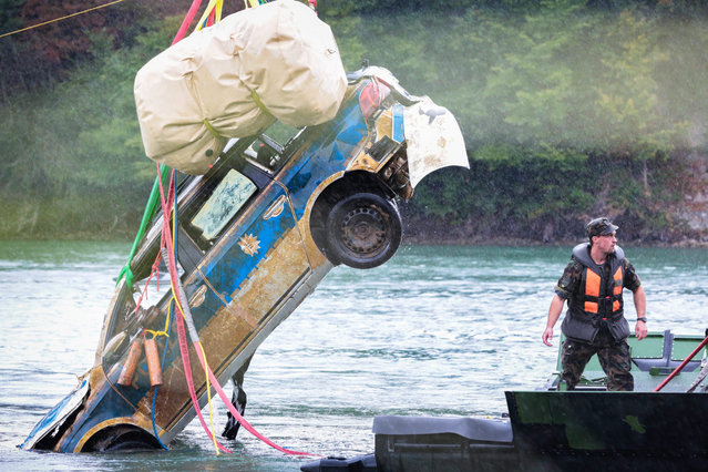 The Swiss army helps to recover a German police car from the Rhine river in Mumpf, Switzerland, 24 August 2015. The vehicle disappeared into the Rhine in June 2013 because the Police officers forgot to apply the handbrake during a police control. A hobby diver discovered the wreck around two kilometers from the accident scene one week ago. (Photo by Pascal Bloch/EPA)