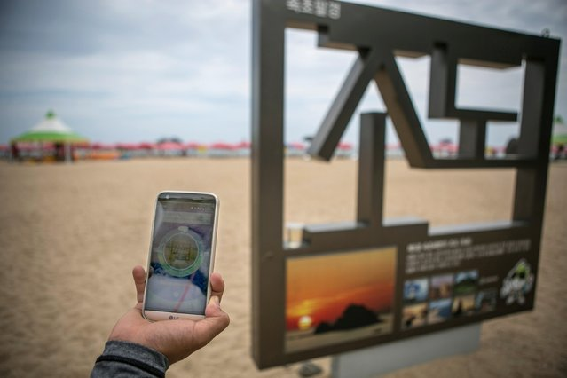 A South Korean youth checks the landmark visible on Pokemon Go application on July 15, 2016 in Sokcho, South Korea. (Photo by Jean Chung/Getty Images)