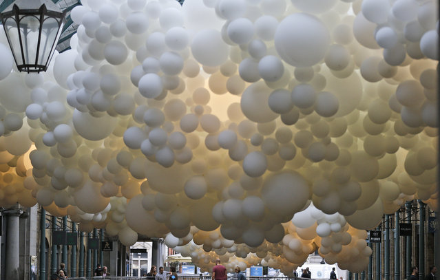 "Balloons of the installation ""Heartbeat"" are seen at Covent Garden Market in London, Thursday, August 27, 2015. ""Heartbeat"" is French artist Charles Petillon's first public art installation and his first ever live work outside of France, uniting modern art with world-class architecture. Weaving its way through the South Hall of the Grade II listed Market Building, ""Heartbeat"" is created from 100,000 white balloons and stretches 54 meters in length and 12 meters in width. (Photo by Frank Augstein/AP Photo)"