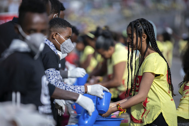 Volunteers, left, provide soap and water for participants to wash their hands against the new coronavirus at a women's 5km fun run in the capital Addis Ababa, Ethiopia Sunday, March 15, 2020. Ethiopia reported on Thursday its first case of the new coronavirus which causes COVID-19. For most people, the new coronavirus causes only mild or moderate symptoms, such as fever and cough but for some, especially older adults and people with existing health problems, it can cause more severe illness, including pneumonia. (Photo by Mulugeta Ayene/AP Photo)