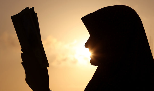 A Palestinian girl reads the Quran, Islam's holy book, at sunset in Gaza City on Friday, July 4, 2014. Muslims throughout the world are celebrating the holy fasting month of Ramadan, refraining from eating, drinking, and smoking from dawn to dusk. (Photo by Hatem Moussa/AP Photo)