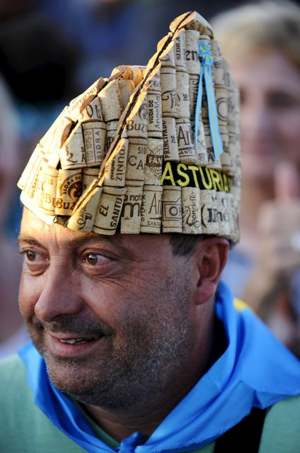 A man with a hat made of cork stoppers takes part in trying to beat the world record of people simultaneously pouring cider during the annual Fiesta de la Sidra Natural (Natural Cider Party) in Gijon, northern Spain, August 28, 2015. (Photo by Eloy Alonso/Reuters)