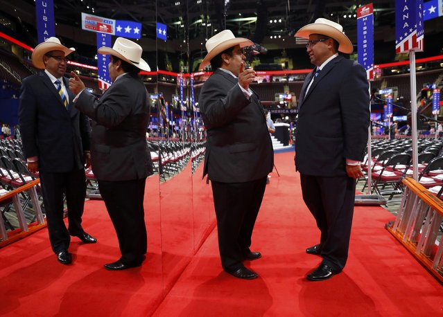 Texas delegates are reflected in a mirror as they talk on the floor during the first day of the Republican National Convention in Cleveland, Ohio, U.S., July 18, 2016. (Photo by Aaron P. Bernstein/Reuters)