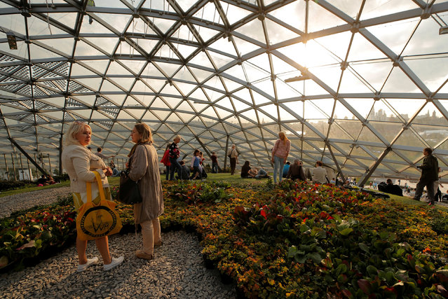 """People rest at a glass dome with a greenhouse (or """"Glass bark"""") at the newly opened Zaryadye Park off Red Square in central Moscow, Russia September 11, 2017. (Photo by Maxim Shemetov/Reuters)"""