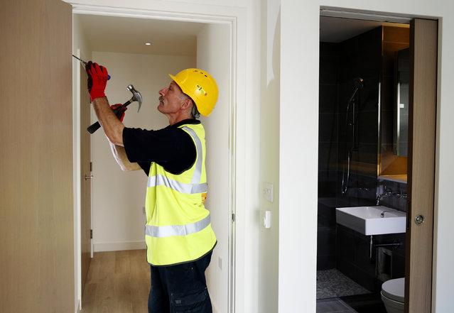 Carpenter Richard Helad adjusts a door in a new apartment constructed by Berkeley Homes in Hackney, northeast London July 22, 2014. (Photo by Luke MacGregor/Reuters)
