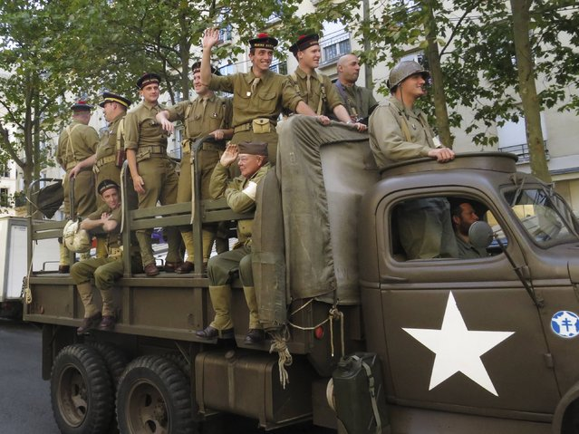 History enthusiasts ride vintage World War Two vehicles during a parade as part of activities to commemorate the 70th anniversary of the liberation of the French capital in WWII, in Paris August 24, 2014. (Photo by John Schults/Reuters)