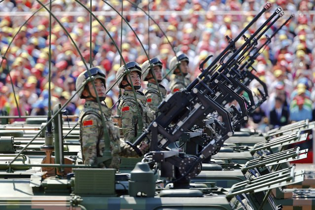 Soldiers of the People's Liberation Army (PLA) of China look from behind their weapons as they arrive at Tiananmen Square during the military parade marking the 70th anniversary of the end of World War Two, in Beijing, China, September 3, 2015. (Photo by Damir Sagolj/Reuters)