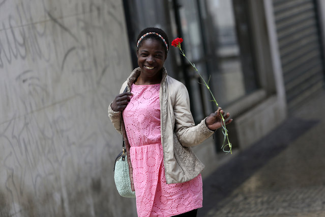 A young woman smiles while carrying a red carnation, symbol of the April 25th Portuguese revolution, in Lisbon's Mouraria neighborhood, Saturday, April 25, 2020. Portugal marks Saturday the anniversary of the 1974 revolution that restored democracy in the country, however due to the coronavirus outbreak this year without the celebrations that usually attract hundreds of thousands. (Photo by Armando Franca/AP Photo)