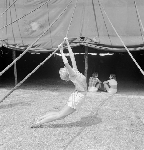 An acrobat practicing with a tent rope while two girls are sitting nearby during a rehearsal for the Ringling Bros. and Barnum & Bailey Circus in Sarasota, FL in 1949. (Photo By Nina Leen/Time Life Pictures/Getty Images)