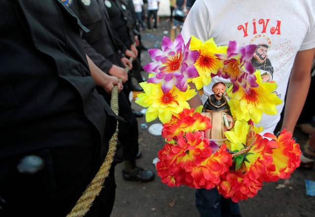 A child carries a figurine of Santo Domingo de Guzman during celebrations honouring the patron saint  in Managua, Nicaragua August 1, 2016. (Photo by Oswaldo Rivas/Reuters)