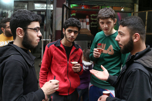 Gymnast Ahmad al-Sawas (2nd R) drinks coffee as he chats with friends along a street in the rebel-held Bustan al-Qasr neighbourhood of Aleppo, Syria March 26, 2016. (Photo by Abdalrhman Ismail/Reuters)